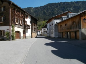 A small lane through the Swiss village of Castrisch. Buildings on either side.