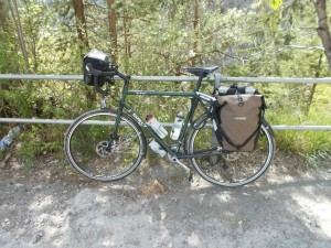 A Surly Disc Trucker fully loaded for touring, leaning against a metal fence.