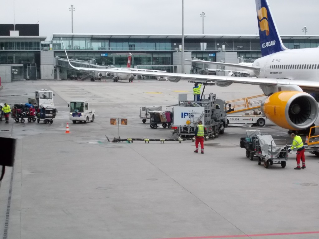 Icelandair aircraft with bike boxes being unloaded down cargo ramp.