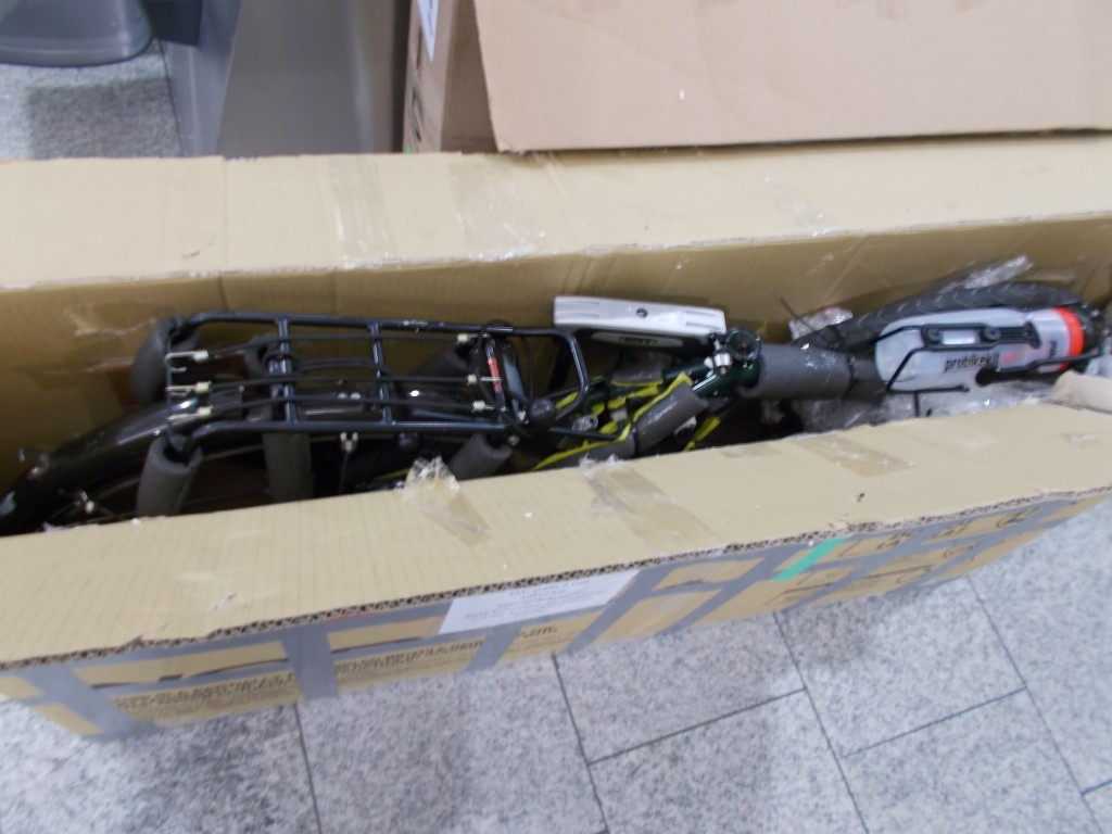 A Surly Disc Trucker disassembled and in a bike box on the floor of the Zürich airport.
