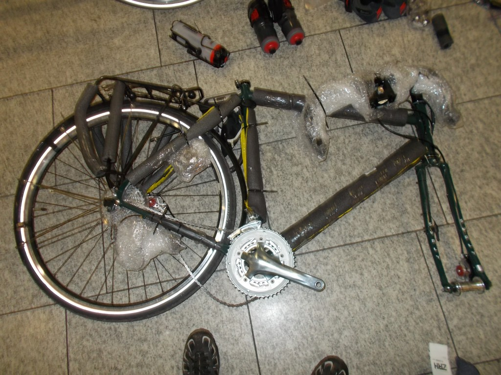 A Surly Disc Trucker bike (green) ready for reassembly on the floor of the Zürich airport.