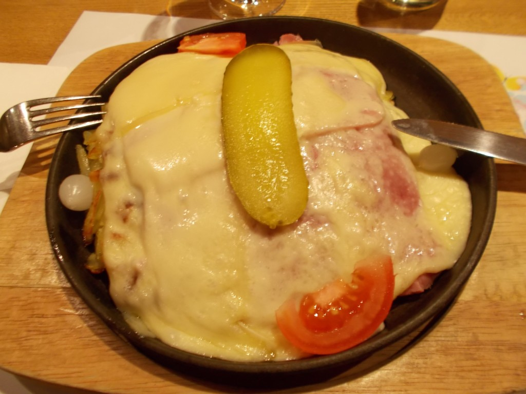 A cast iron plate filled with rösti, cheese, fresh tomato, and a pickle.