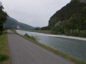 A straight section of bike path bordering the Rhine river in the river valley.