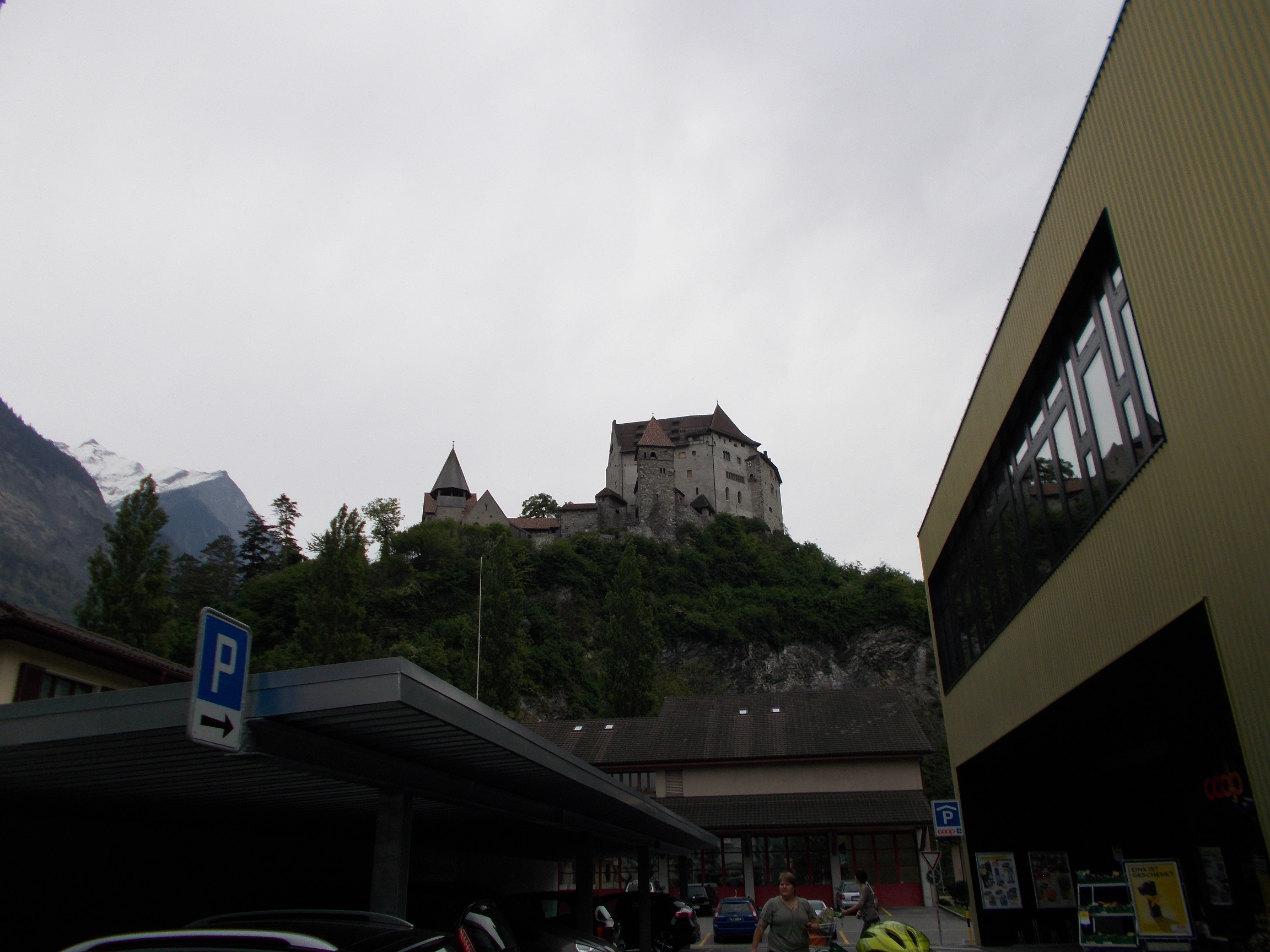 Picture of a large castle atop a hill, photographed from below.