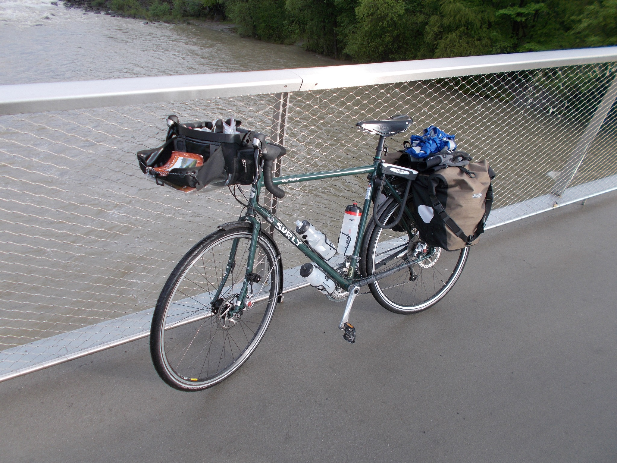 A green Surly Disc Trucker, slightly wet, drying out on a bridge.