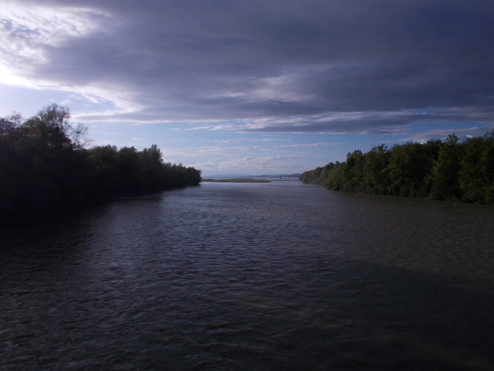 A wide shot of a river leading into a lake, with treed areas on either side. Clouds above.