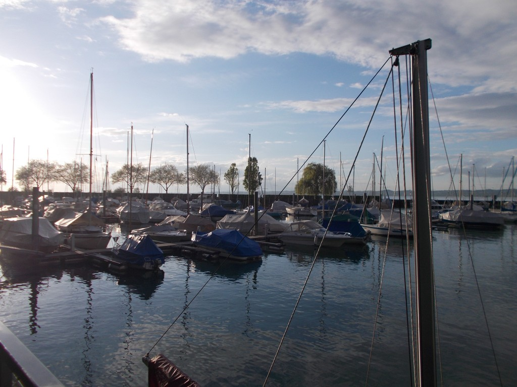 Boats in a small harbour with Lake Constance visible in the background.