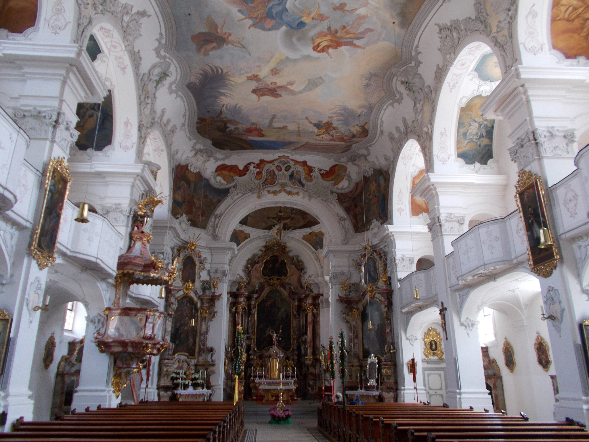 A beautifully painted church interior with a vast painting on the ceiling taken at Münster Unserer Lieben Frau in Lindau, Germany.