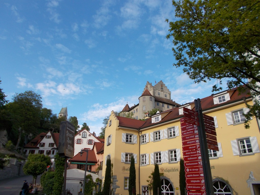 Colorful buildings with a large castle in the background in Meersburg, Germany.