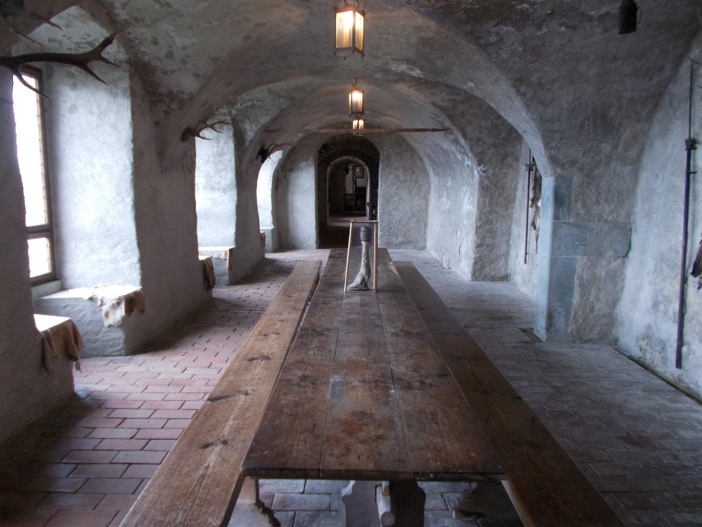 A long hallway with a long table running down it. Light from outside beams in from the left. Walls made of stone. Photo taken inside Burg Meersburg in Meersburg, Germany.