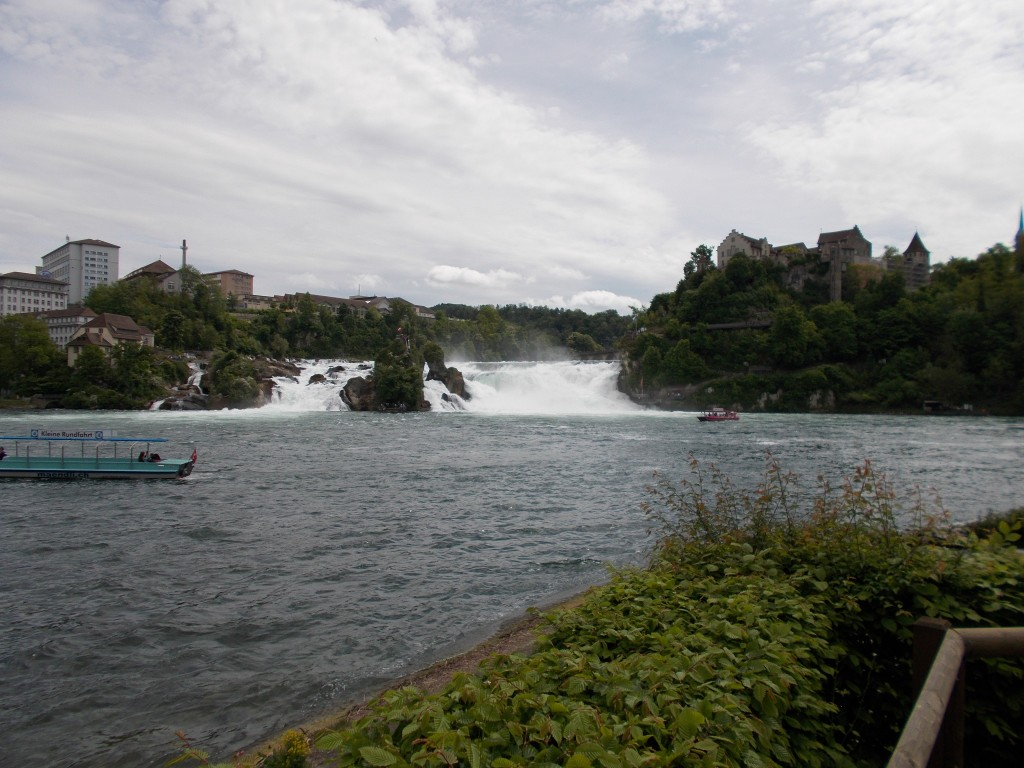 A wide angle shot of a large waterfall on the Rhine river. A castle is also visible on a hilltop.