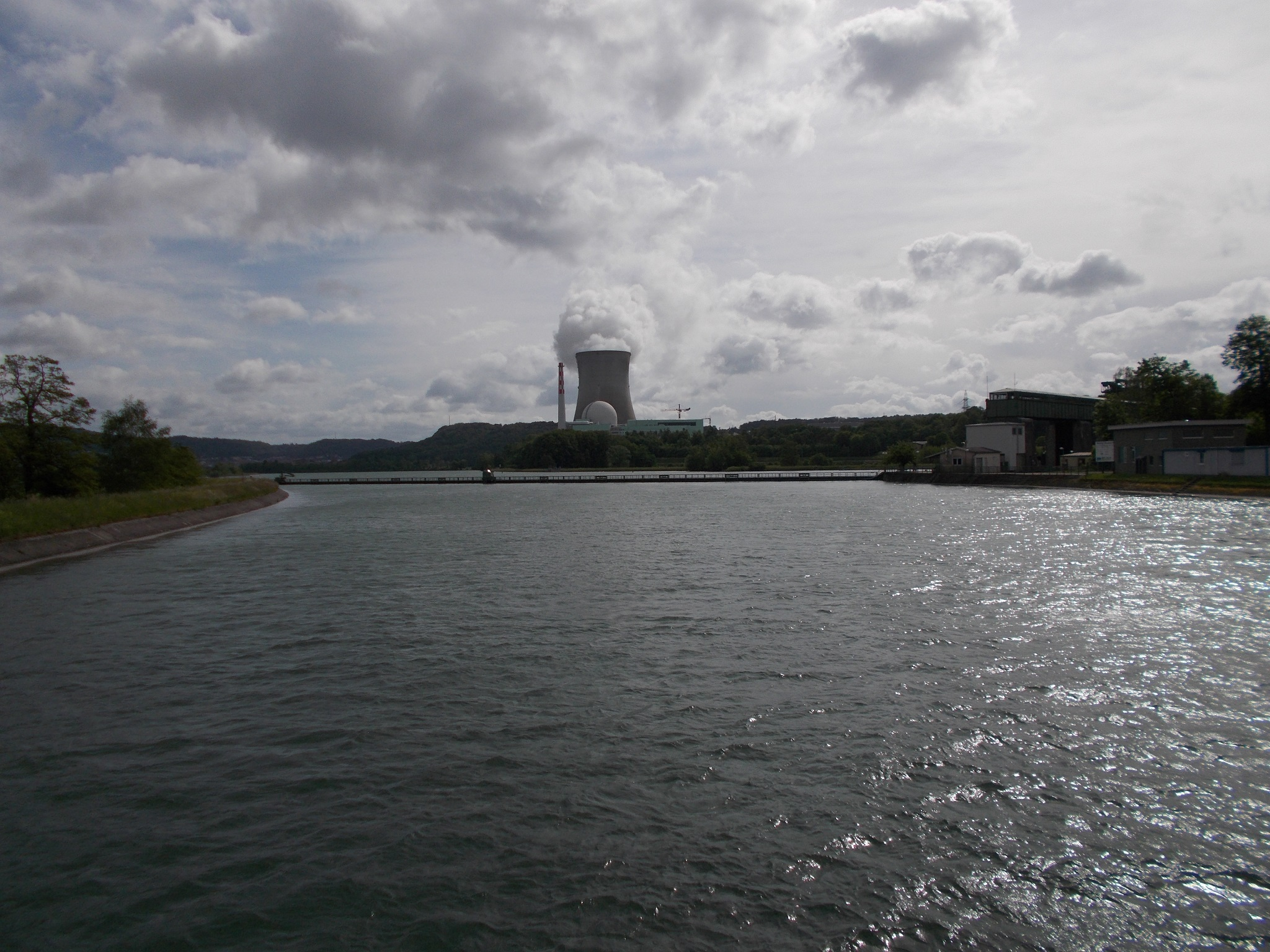 The Rhine river with the cooling tower of a nuclear power plant visible in the distance.