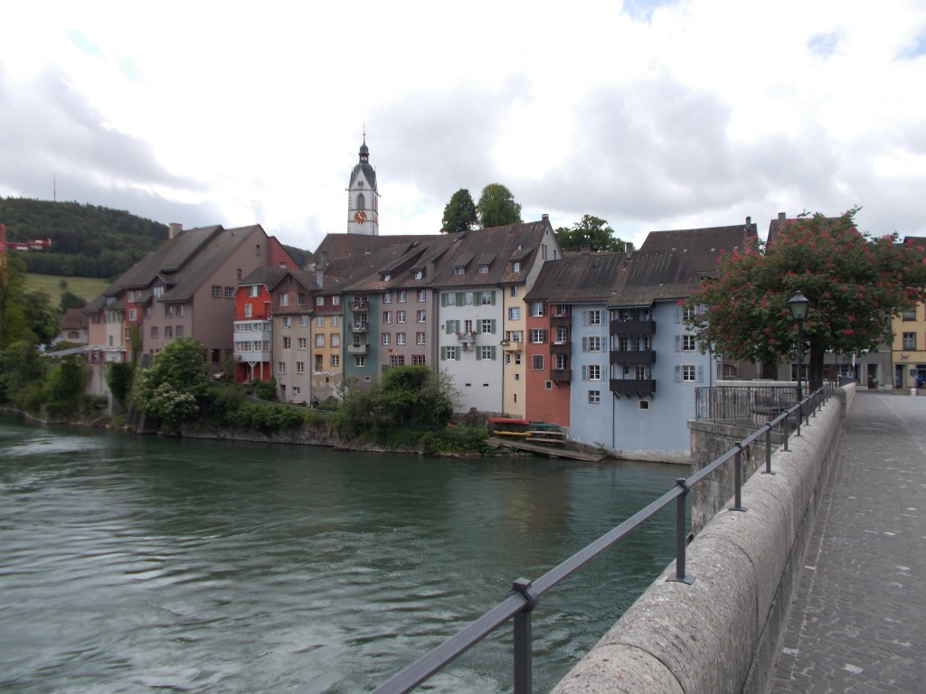 A row of colourful buildings at the edge of the Rhine river photographed from a bridge.