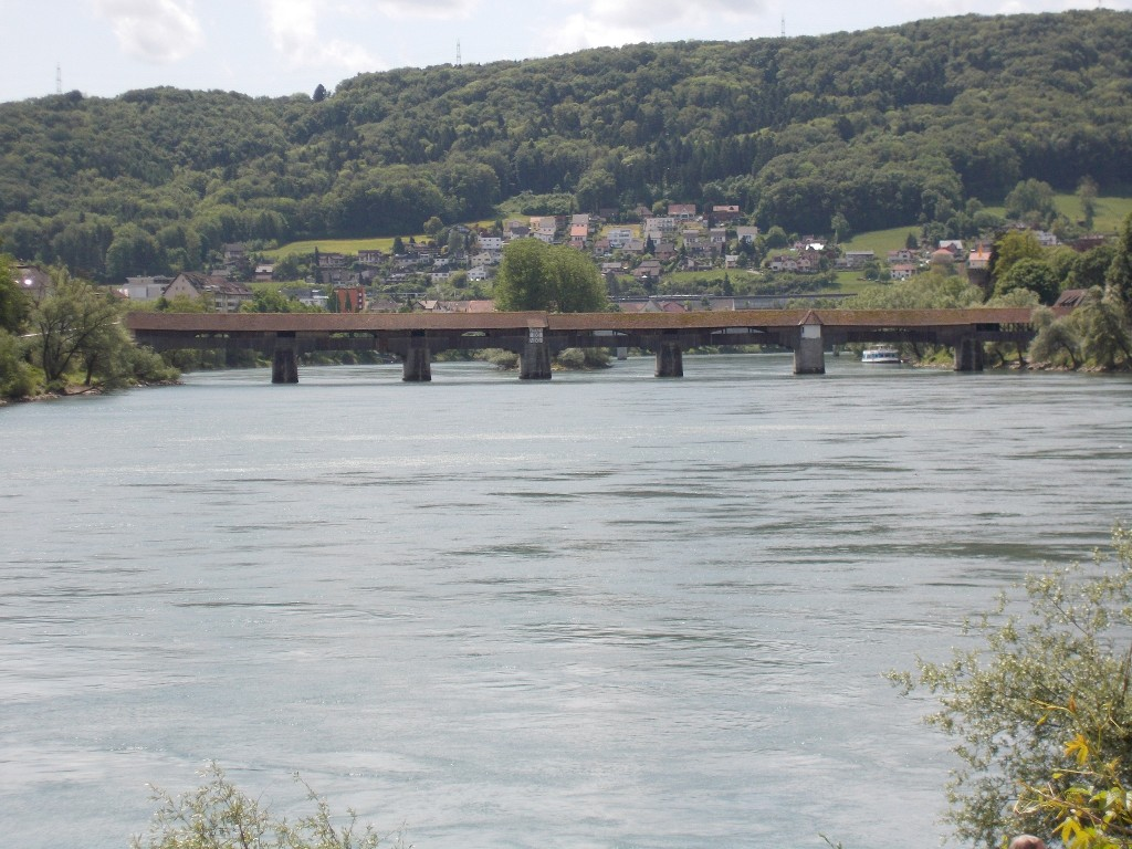 A very long covered bridge spanning the Rhine river with a town in the background.