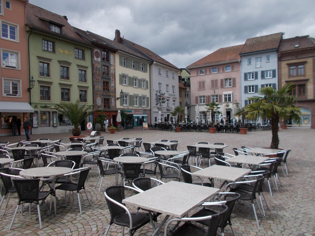 An attractive town square with tables set out for the local cafes. Colourful buildings are visible in the background.