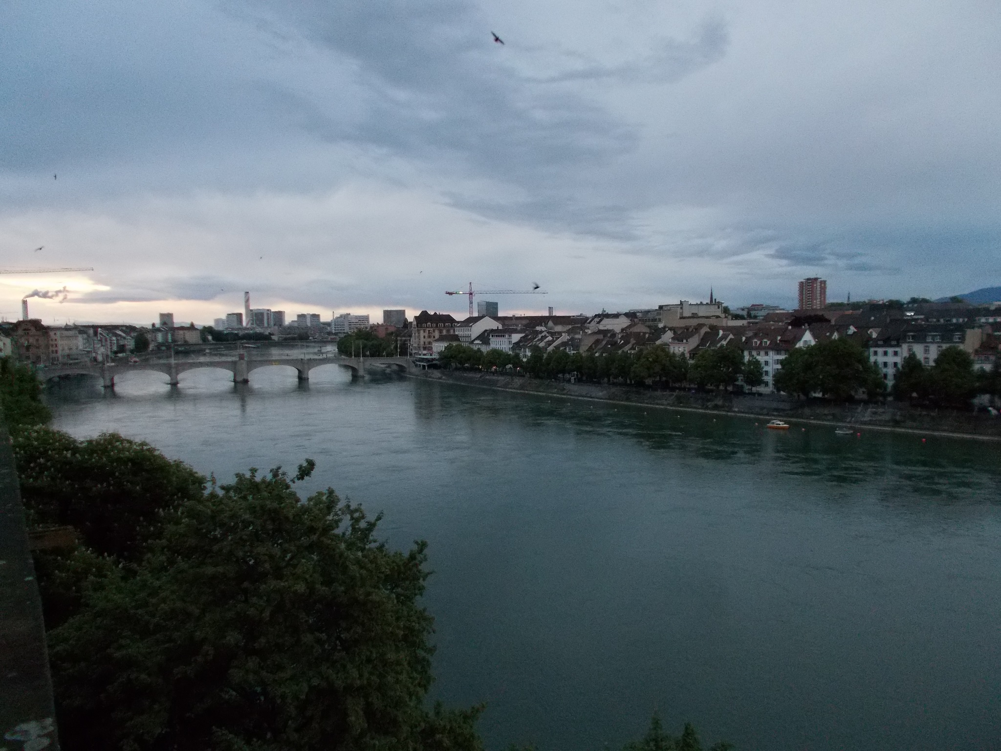 A wide river with high density housing along its banks. A bridge is visible in the distance and clouds fill the skies above.