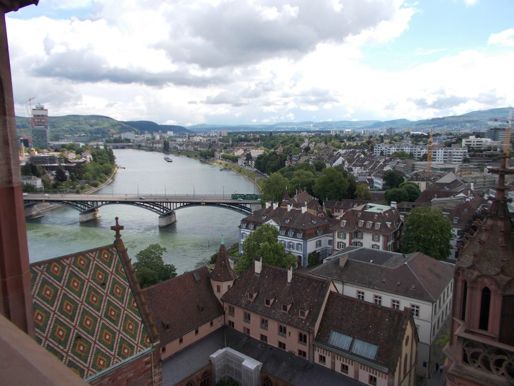 A large river running through Basel, Switzerland, a spire of a cathedral visible in the foreground.