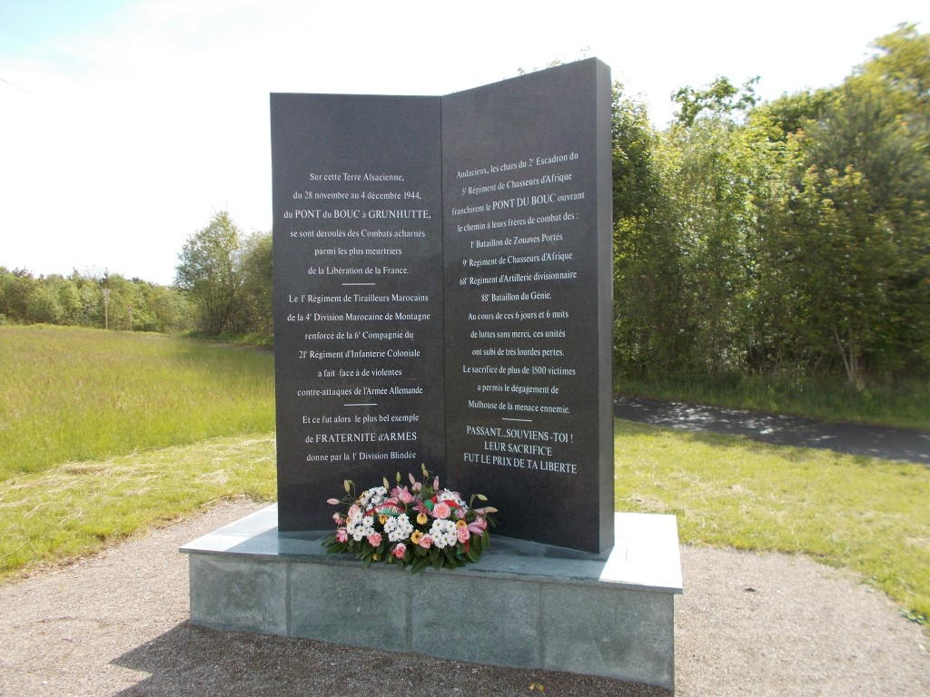 A memorial to fallen soldiers with a path and forest in the background.