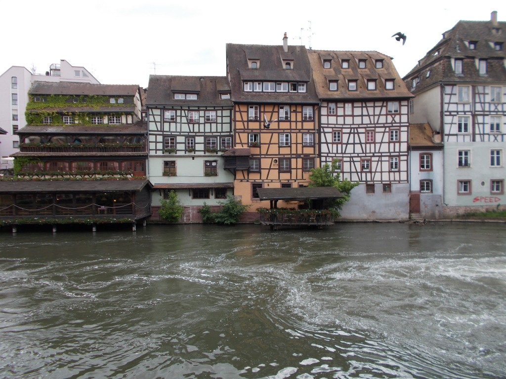 Beautiful French buildings built directly on the waters edge of a waterway running through Strasbourg, France.